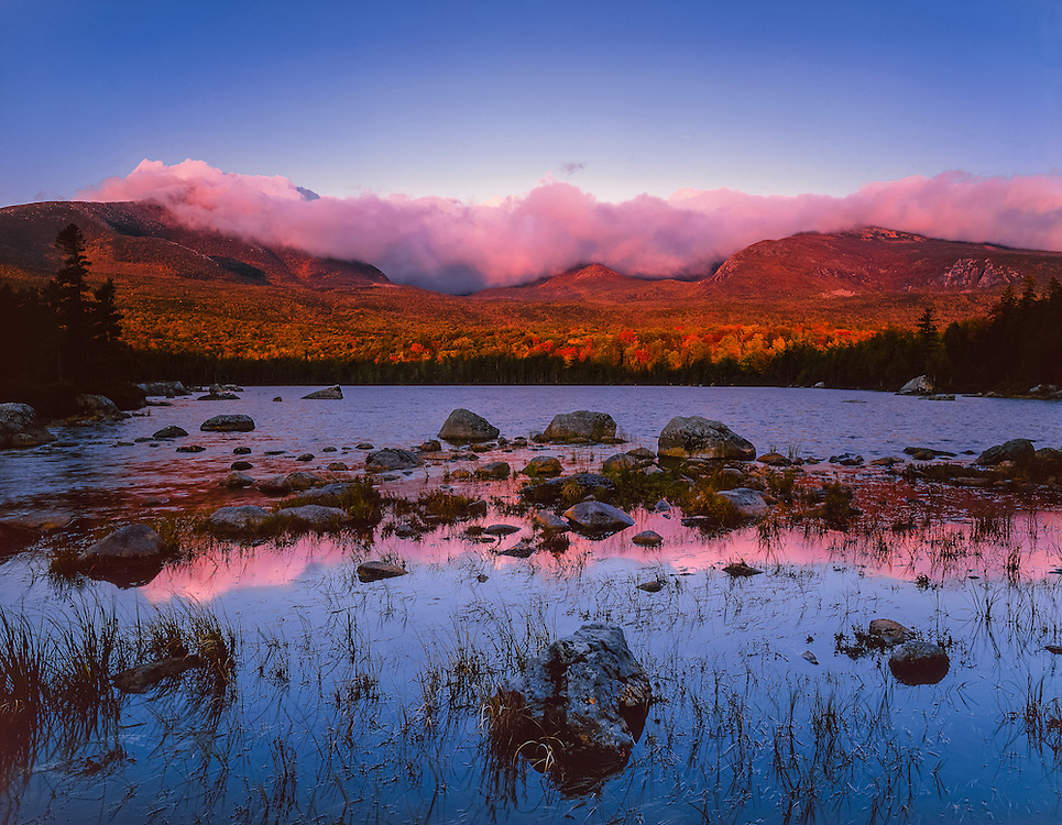 Storm clouds gathered at mountain tops, pink light at dawn, reflections in pond, Baxter State Park, ME