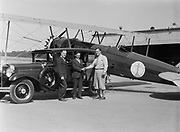 """9904-XE. """"Raffaele Mauillari, the """"Flying Iceman"""" of New York City, round-the-world racer, with Studebaker's President. On the left is Oregonian reporter Larry Barber, who wrote and edited the automobile features in the Sunday paper. The car is a new Studebaker Dictator 8, and the plane is a Boeing Pacific Air Transport mail plane. Photo taken fall 1929 at Swan Island airport in Portland, Oregon."""
