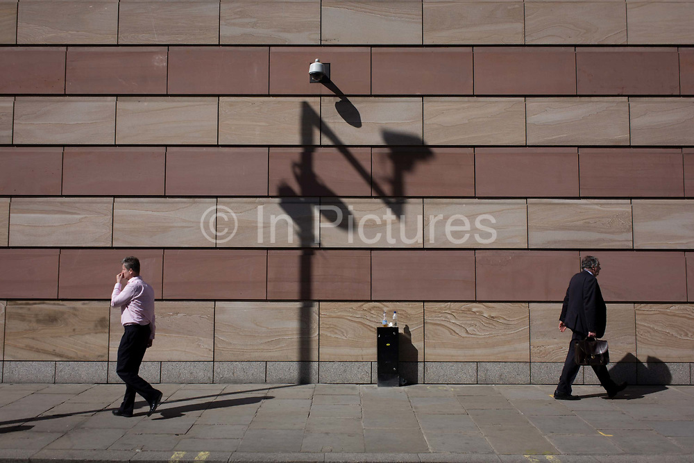 Businessmen pas each other below a CCTV camera with the shadow of a traffic camera on the wall of a modern office building in the City of London, the capital's financial district. The capital's financial district - aka the Square Mile - is the oldest, historic quarter, home to banking, financial and insurance institutions and therefore victim to street security problems as well as white collar crime. The City is therefore one of the most covered areas in Britain for CCTV surveillance cameras, introduced during IRA terrorism activity in the 90s but now there to monitor the streets.