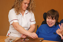 Client with Cerebral Palsy being helped by carer doing craft activity at a resource for people with physical and sensory impairment.
