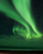 The Northern Lights seem to flow in the sky above the Hudson Bay near Churchill, Manitoba Canada.
