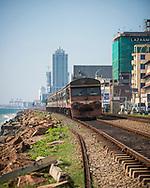 A passenger train travels along a railroad track beside the ocean in Colombo, Sri Lanka