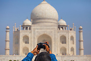 Man holding up his camera to photograph the Taj Mahal in the distance