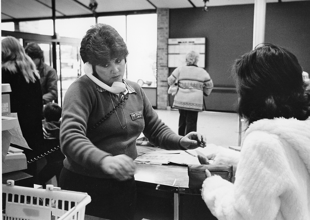 ©1991  Woman working at supermarket checkout in Austin, Texas.  no MR