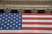 a very large American flag draped over the front at the New York Stock Exchange