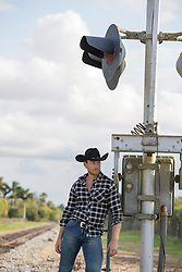 cowboy leaning against a railroad track signal