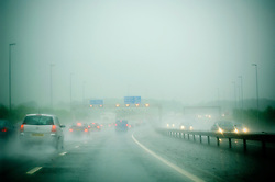 Driving through heaving rain and spray on the M6 motorway, Preston, Lancashire, England, UK.