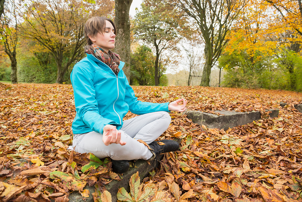 Woman meditating in lotus positing while sitting on rock in autumn scenery