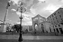 Piazza S.Oronzo Lecce con anfiteatro romano e sedile in bianco e nero con cielo nuvoloso