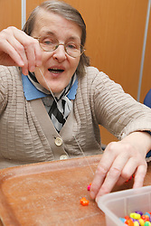Client doing craft activity stringing beads at a resource for people with physical and sensory impairment.