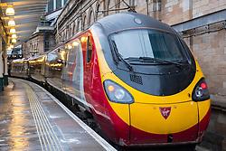 Virgin Trains Pendolino locomotive to London Euston  on West Coast Main line  at platform at Waverley Station in Edinburgh, Scotland, United Kingdom