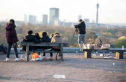 © Licensed to London News Pictures. 18/04/2021. London, UK. As members of the public gather to watch the sun rise, litter remans strewn across the top of Primrose Hill in North London despite the park being closed from 10pm last night. A curfew has been put in to place at the park over the weekend  to prevent large gatherings in the evening. Photo credit: Ben Cawthra/LNP