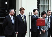 © Licensed to London News Pictures. 21/03/2012. Westminster, UK. British Chancellor of the Exchequer George Osborne, pictured with his staff, holds his red ministerial box as he poses for pictures outside 11 Downing Street in London, on March 21, 2012. The Chancellor is expected to raise the amount of money people can earn before income tax takes hold and impose a new levy on the purchase of expensive homes. Photo credit : Stephen SImpson/LNP