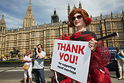 Demonstrator drag queen holds a placard promoting equal marriage rights outside Parliament in London, UK, ahead of the final reading of the 'Marriage Bill 2012-13 to 2013-14'. A Bill to make provision for the marriage of same sex couples in England and Wales.
