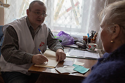 Dr Andre Poliakov consults with an elderly patient at an MSF mobile clinic in the  village of Sukodolsk near to Lugansk.