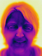 Thermogram of a woman. This image is part of a series including a matching image in visible light.   The different colors represent different temperatures on the object. The lightest colors are the coldest temperatures, while the darker colors represent a hotter temperature.  Thermography uses special cameras that can detect light in the far-infrared range of the electromagnetic spectrum (900?14,000 nanometers or 0.9?14 µm) and creates an  image of the objects temperature..