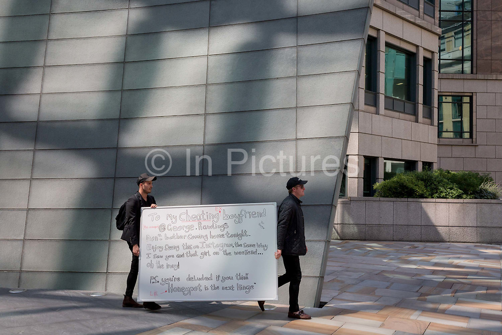 Two men carry a white-board through Broadgate as part of a new Dating app start-ups PR stunt purporting to be written by a jealous lover to her cheating partner who works nearby in the City of London, the capitals financial district - aka the Square Mile, on 8th August, in London, England.