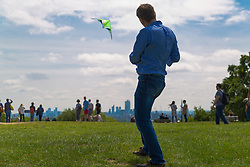Against the backdrop of the city and taking advantage of the bank holiday Sunday sunshine and breeze, accountant Oliver Davidson, 47, flies his powerful Tim Benson Kite on Parliament Hill on Hampstead Heath. London, May 26 2019.