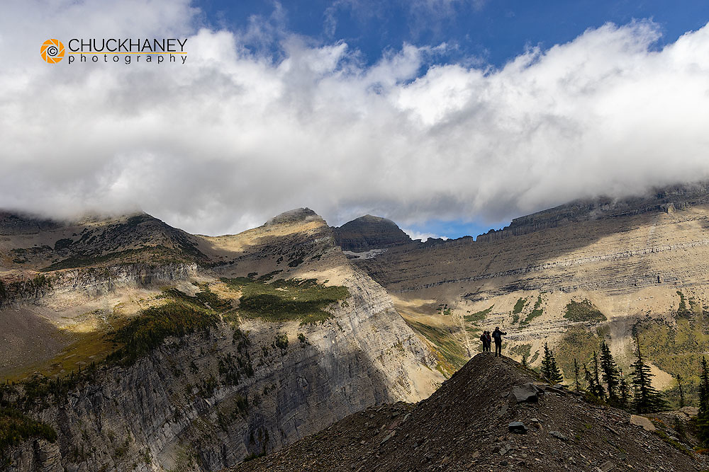 Hikers silhouetted below Swiftcurrent Mountain in Glacier National Park, Montana, USA