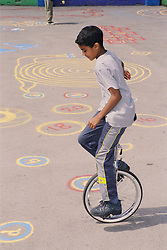 Young boy riding unicycle around playground,