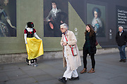 People passing a Snow White living statue sculpture in Trafalgar Square, London, UK. In this tourism area of London many of these real statues stand collecting money. Here the juxtaposition of a hoarding with portraits of old masters at the National Gallery, and passrs by creates a weird scene.