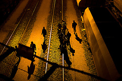 © Licensed to London News Pictures. 09/08/2015. Calais, France. A group of migrants running along the train tracks of the  Eurotunnel terminal at Frethun near Calais, northern France. Hundreds of migrants attempt to illegally access the Eurotunnel complex each night in order to board a train and reach the UK. Photo credit: Ben Cawthra/LNP