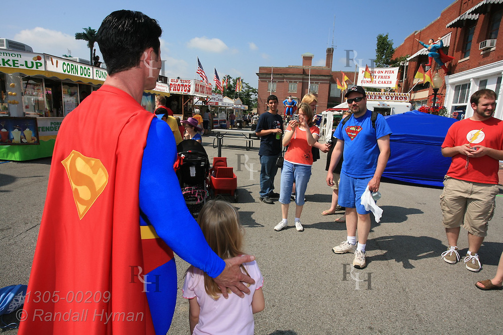 Superman devotee, Danny Kelley, dresses the part while posing with little girl for photo at Superman Celebration; Metropolis, Illinois.