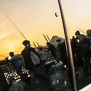 Sunset reflection on a car window of fishermen on the Galata Bridge and a mosque on the skyline.