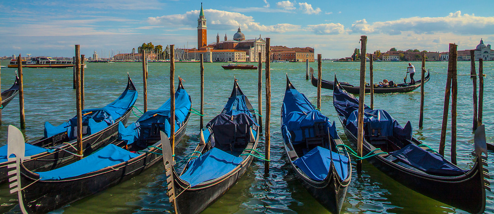 A row of gondolas parked in the Venice lagoon with Guidecca Island in the distance