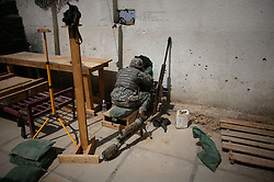 A sniper attached to Charlie Co. 1-26 Infantry 1st Infantry Division peers through a gun port as while he guards against attacks on the Joint Security Station in central Adhamiya on Thursday April 27, 2007.