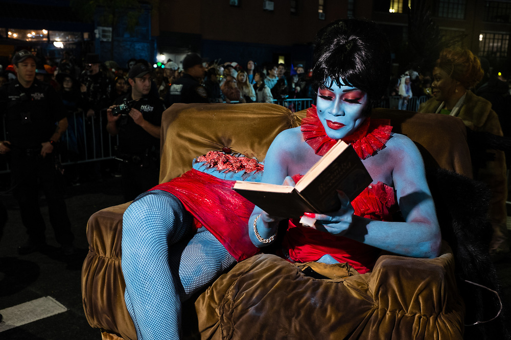 New York, NY - 31 October 2019. the annual Greenwich Village Halloween Parade along Manhattan's 6th Avenue. A woman calmly reads on a sofa, her upper torso beside her lower extremities, her body severed at the waist, her guts visible.