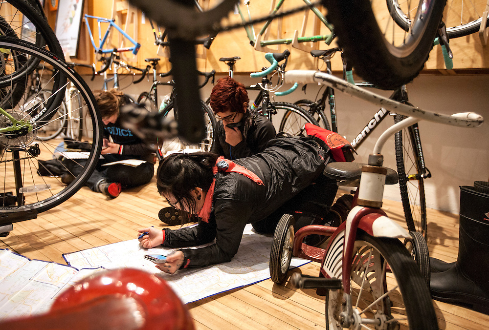 Ayako Osaki, foreground, and Sheida Ferabi Iverson map out their routes at One on One Bicycle Studio before the start of Stupor Bowl 17 in Minneapolis February 1, 2014.
