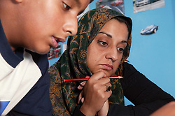 Mother helping her son with his homework,