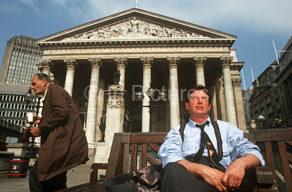 City workers enjoy a lunchtime siesta in summer sunshine under solid Corinthian pillars of the Royal Exchange in City of London. With his tie askew and loosened around his neck, a successful businessman sits on a bench below the war memorial and tall pillars of this Victorian market building in the heart of London's financial district. Alongside is an older, less prosperous man whose rumpled coat gives us the sense that he might be less accomplished than the younger gentleman. There is a heat wave in the capital and officer workers have come out into the sunshine to unwind and snatch a quick sleep in parks and open spaces. The neo-Romanesque Royal Exchange building also has Doric and Ionic columns with their ornate stonework, strong lintels with carvings featuring the design by Sir William Tite in 1842-1844 and opened in 1844 by Queen Victoria.