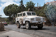 A UN vehicle, part of the United Nations Interim Force in Lebanon (UNIFIL) mission, drives through a village in southern Lebanon. Photographed through the window of a car.
