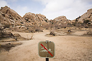 A park sign prohibits swimming in the reservoir, pictured dry, created by Barker Dam in Wonderland of Rocks, Joshua Tree National Park, California. Built by cattle ranchers, the dam holds back rain water, a precious commodity in the desert.
