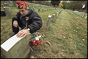 At Cypress Hills National Cemetery Leatherneck veteran James Burke placing a Marine Corps Globe and Anchor and burial flags on the grave of Dan Daly in Queens, NY.