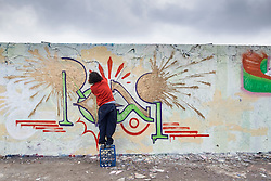 Man painting graffiti on wall at Mauer Park in Prenzlauer Berg in Berlin Germany