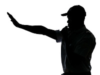 An afro American traffic cop making stop gesture while blowing whistle in studio on white isolated background