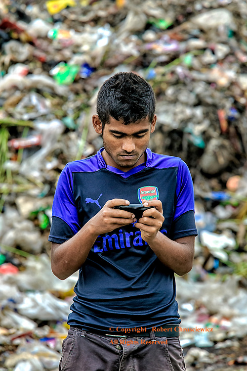 Texting Garbage: A young man stands engrossed, texting on his cell phone,  oblivious to the expansive garbage dump that surrounds him, Mymensingh Bangladesh.