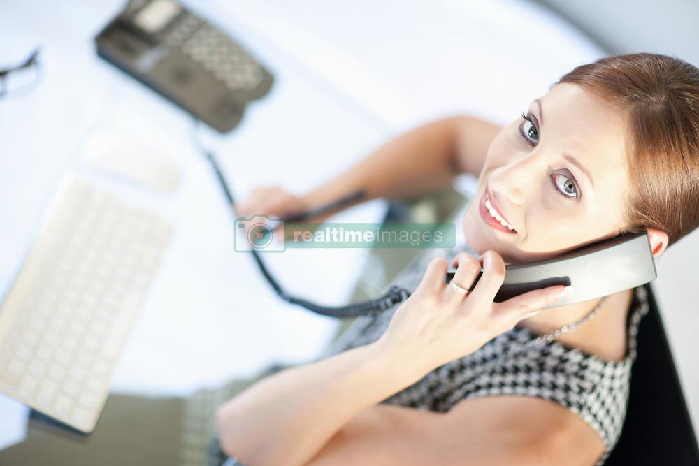Businesswoman talking on phone at desk (Credit Image: © Image Source/Albert Van Rosendaa/Image Source/ZUMAPRESS.com)