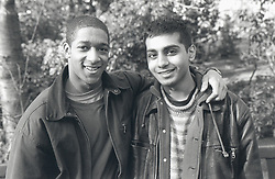 Two young men with arms around each other smiling,