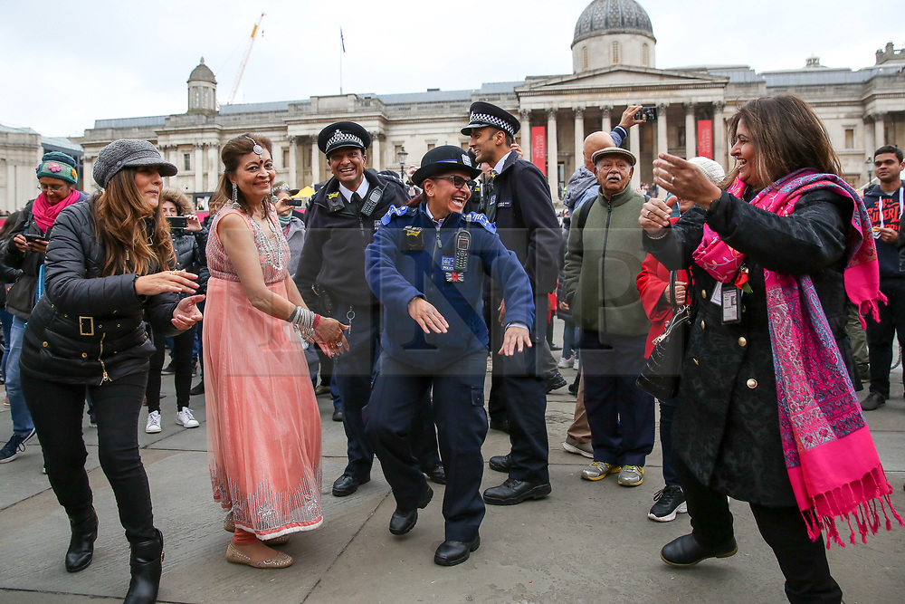© Licensed to London News Pictures. 03/11/2019. London, UK. Police officers are seen dancing with members of public in Trafalgar Square to celebrate Diwali - the festival of light. Hundreds of Hindus, Sikhs, Jains and people from all communities attend Diwali celebrations in London's Trafalgar Square. Diwali s celebrated each year with a free concert of traditional, religious and contemporary Asian music and dance. Photo credit: Dinendra Haria/LNP