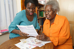 Mother and daughter sorting out the bills.