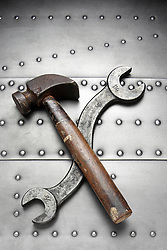 Wrench and hammer on riveted metal