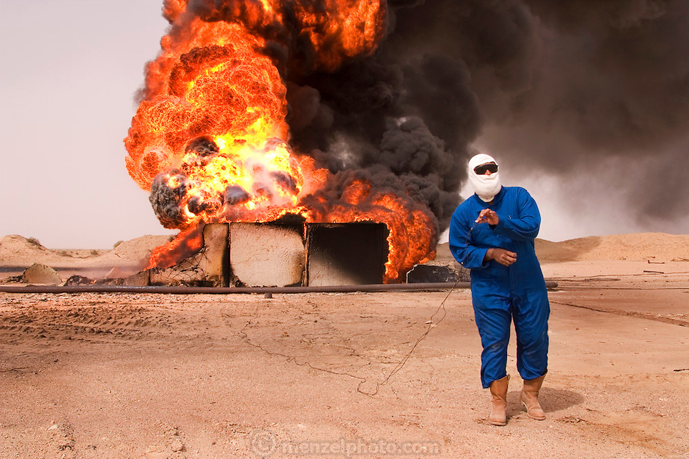 Aisa Bou Yabes, head of the Kuwait Oil Company firefighting team dispatched to southern Iraq inspects damage to oil well heads in Iraq's Rumaila field. He is holding a wire used by retreating Iraqi troops to detonate explosives and set this oil well on fire in the southern Iraq Rumaila oil field. The wells were set on fire when the US and UK invasion began. Seven or 8 wells were set ablaze but at least one other was detonated but did not ignite. The Rumaila field is one of Iraq's biggest with five billion barrels in reserve. Rumaila is also spelled Rumeilah.
