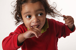 Close up of an anxious looking toddler tugging his hair and sucking his finger,