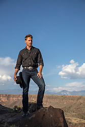 cowboy standing on the edge of a cliff