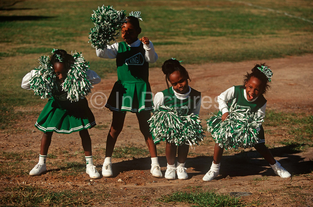 Cheeky young 1990s Afro-American cheerleader girls practice their routine at the Bedford-King Recreation Center, on 5th November 1995, in Atlanta, Georgia USA.