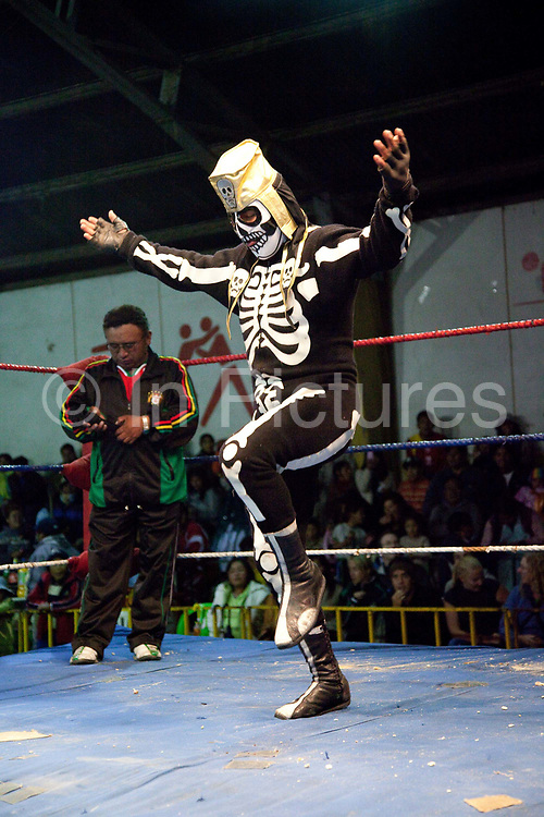 Skeleton wrestler in ring. Lucha Libre wrestling origniated in Mexico, but is popular in other latin Amercian countries, including in La Paz / El Alto, Bolivia. Male and female fighters participate in the theatrical staged fights to an adoring crowd of locals and foreigners alike.